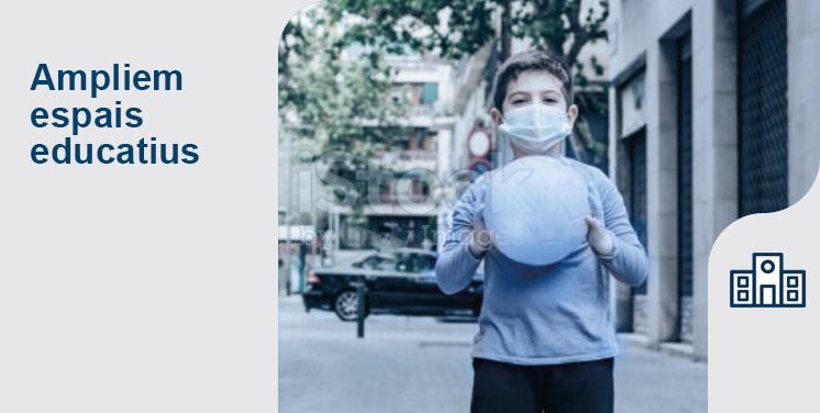 Ampliem espais educatius. Fotografia d'un nen amb mascareta i una pilota al carrer
