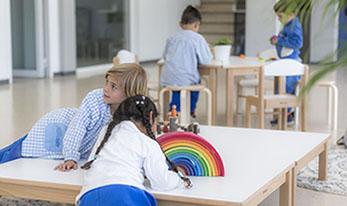 Interior d'aula on es veuen infants jugant